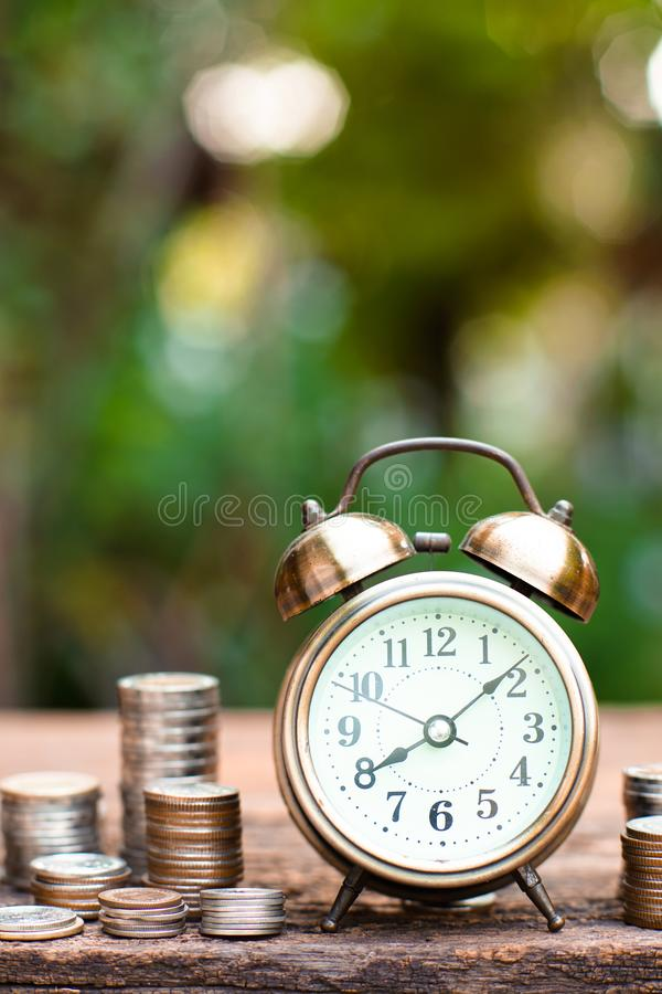Despertador de oro del vintage con las pilas de moneda Hora y dinero para el concepto financiero imagenes de archivo