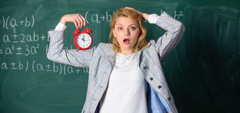 Despertador del control del profesor de la mujer Concepto del horario de las lecciones Hora para la rotura El tiempo tiene materi fotografía de archivo