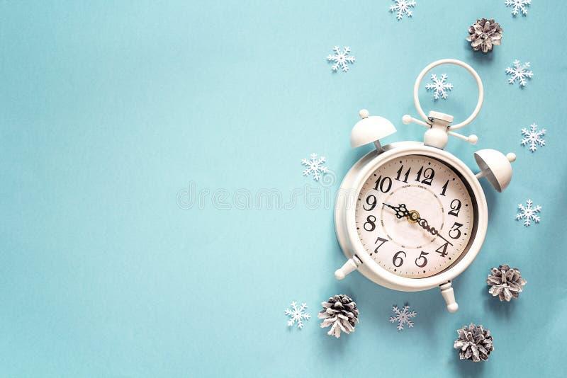 Despertador del invierno con el cono del pino y espacio de la copia en backgro azul foto de archivo libre de regalías
