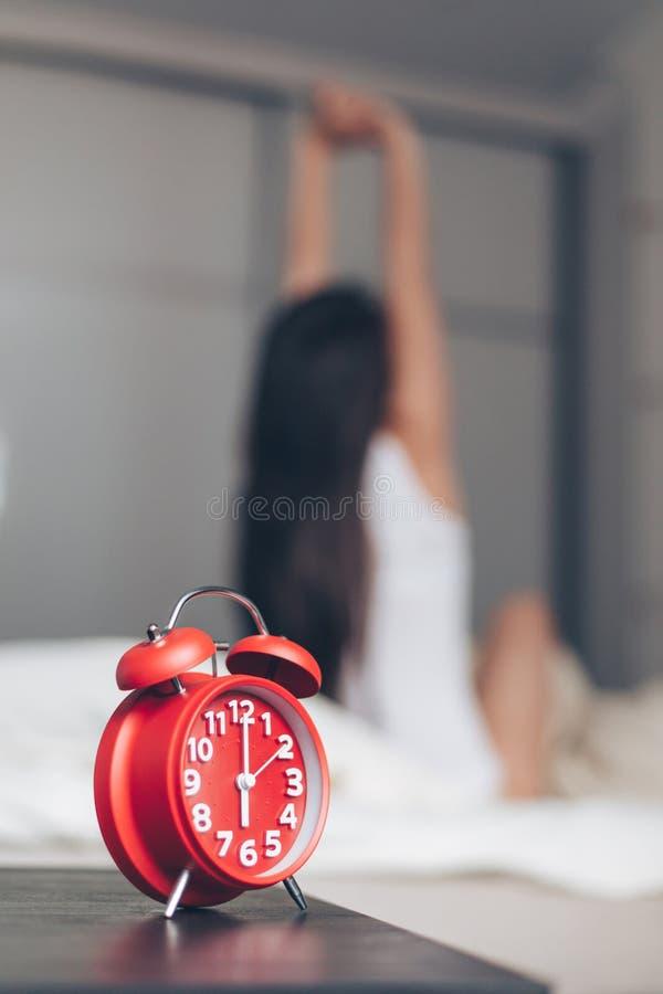 Despertador do close up que tem um bom dia com a mulher feliz do fundo que estica na cama foto de stock royalty free