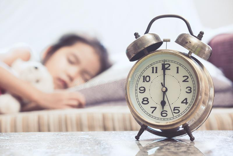 Despertador do vintage na menina asiática bonito da criança que dorme na cama fotos de stock royalty free