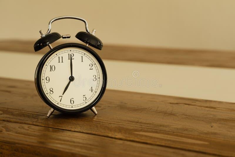 Despertador do vintage na tabela de madeira rústica Mostras 7 horas fotografia de stock royalty free
