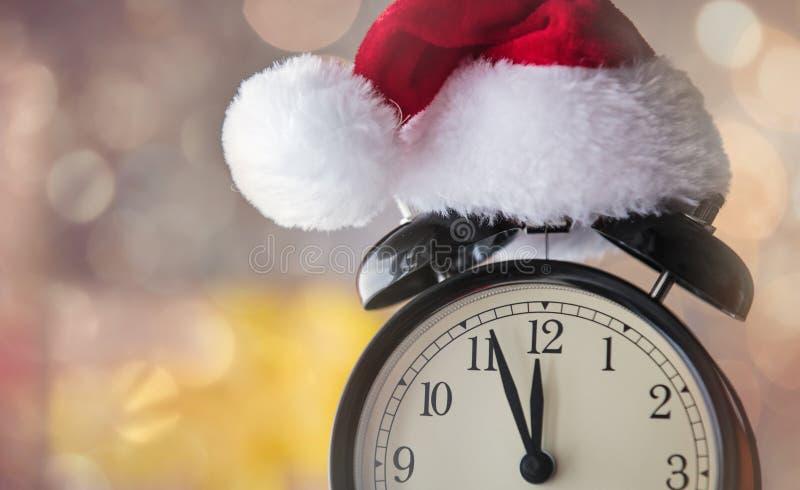 Despertador do vintage no chapéu de Santa Claus com presente do Natal imagem de stock