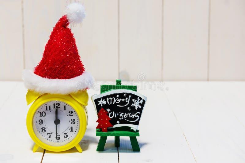 Despertador e chapéu de Papai Noel na madeira foto de stock royalty free
