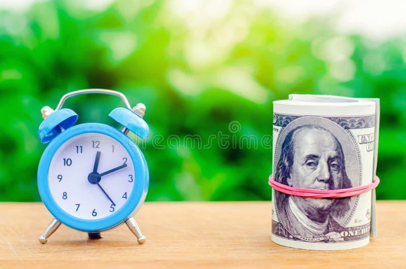 Despertador e dinheiro no fundo verde do bokeh O conceito de Tempo é dinheiro ideias financeiras do negócio saving financeiro fotografia de stock royalty free