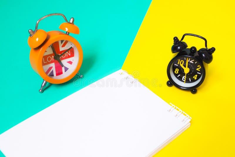 Despertador e livro de nota no fundo colorido com azul, o verde e o amarelo fotografia de stock royalty free