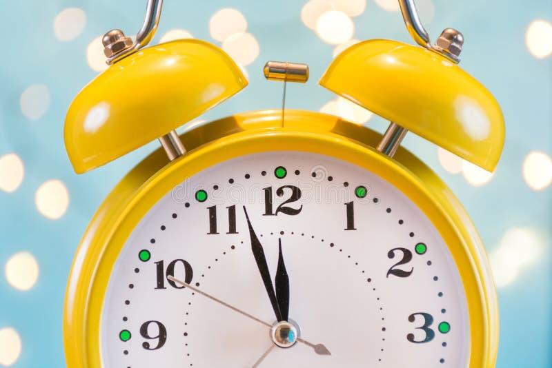 Despertador e luzes de Natal retros velhos no fundo borrado azul imagem de stock royalty free