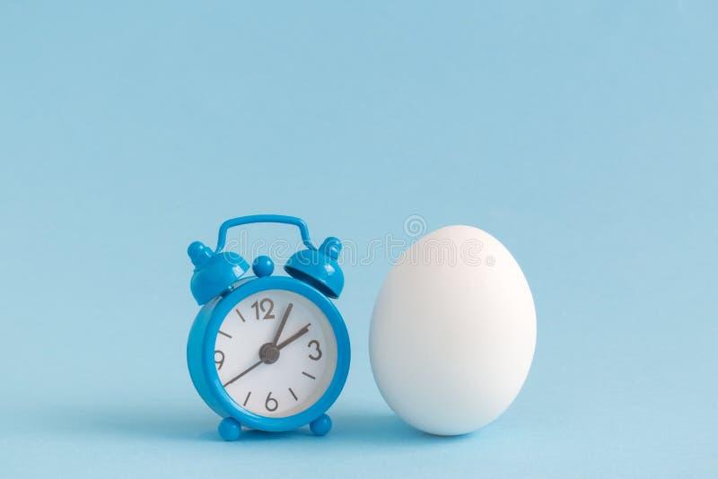 Despertador e ovo isolados no azul Espaço para a cópia Conceito minimalistic da vida da Páscoa ainda fotografia de stock