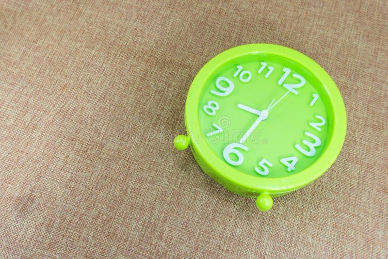 despertador el medio ocho o reloj o el 8:30 a del ` de la harpillera del fondo de la demostración marrón M imagen de archivo libre de regalías