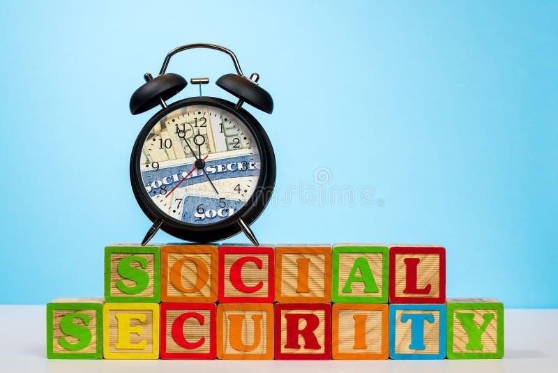 Despertador em blocos de madeira para a segurança social foto de stock royalty free