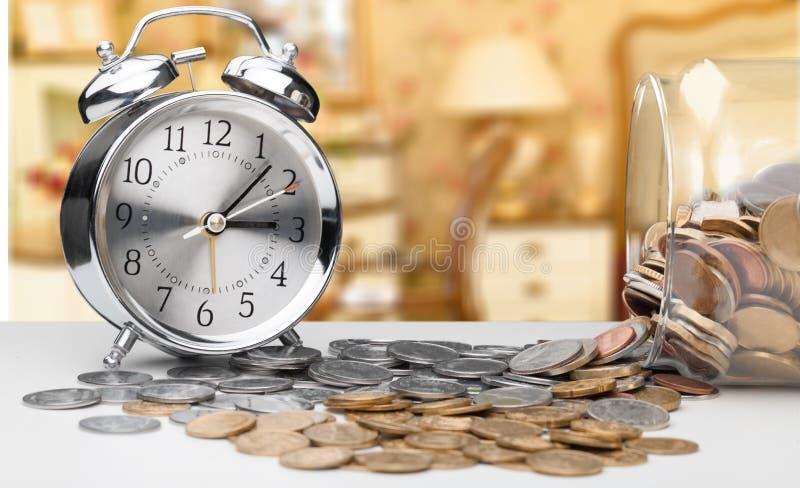 Despertador em moedas foto de stock