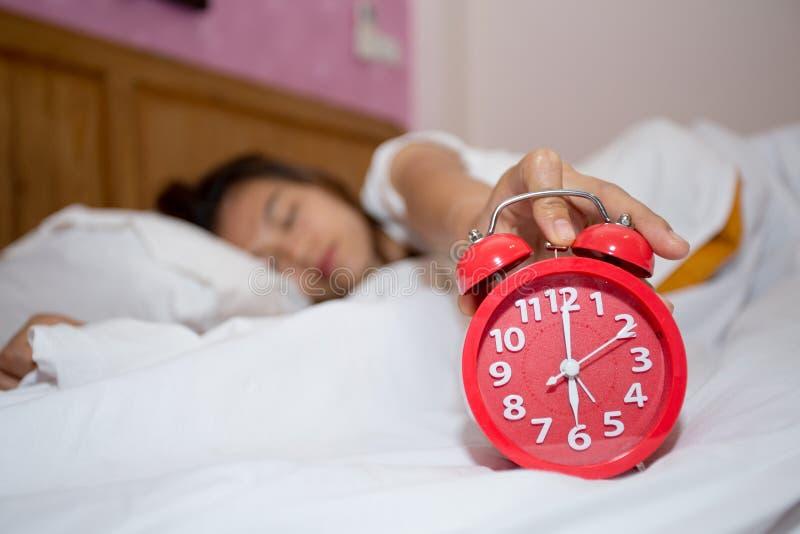 Despertador en dormitorio con intentar perezoso el dormir de la mujer parar fotografía de archivo