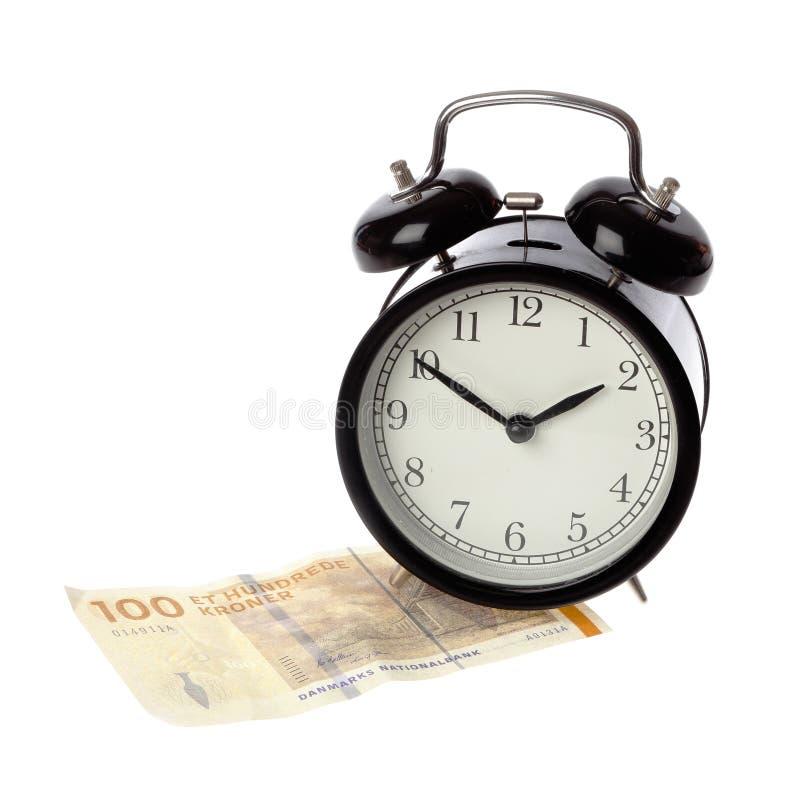 Despertador en el dinero danés foto de archivo