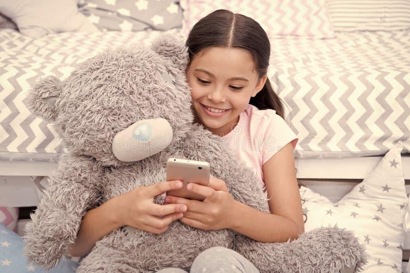 Despertador estabelecido ou notifica??o A crian?a da menina senta-se na cama com o urso de peluche em seu quarto A crian?a prepar foto de stock royalty free