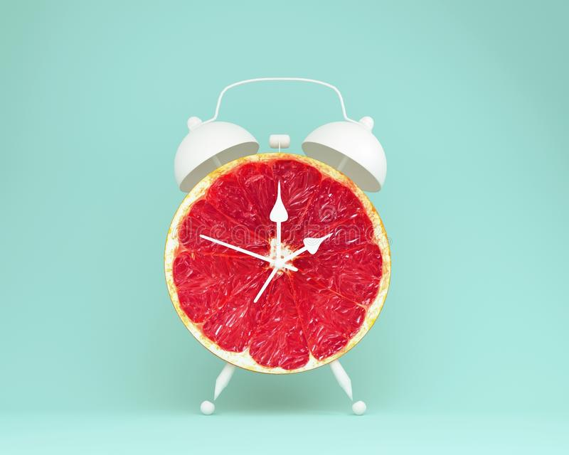 Despertador fresco de la rebanada del pomelo de la disposición creativa de la idea en la goma fotografía de archivo