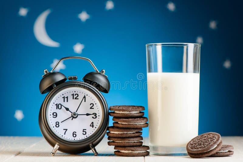 Despertador, galletas y leche imagenes de archivo