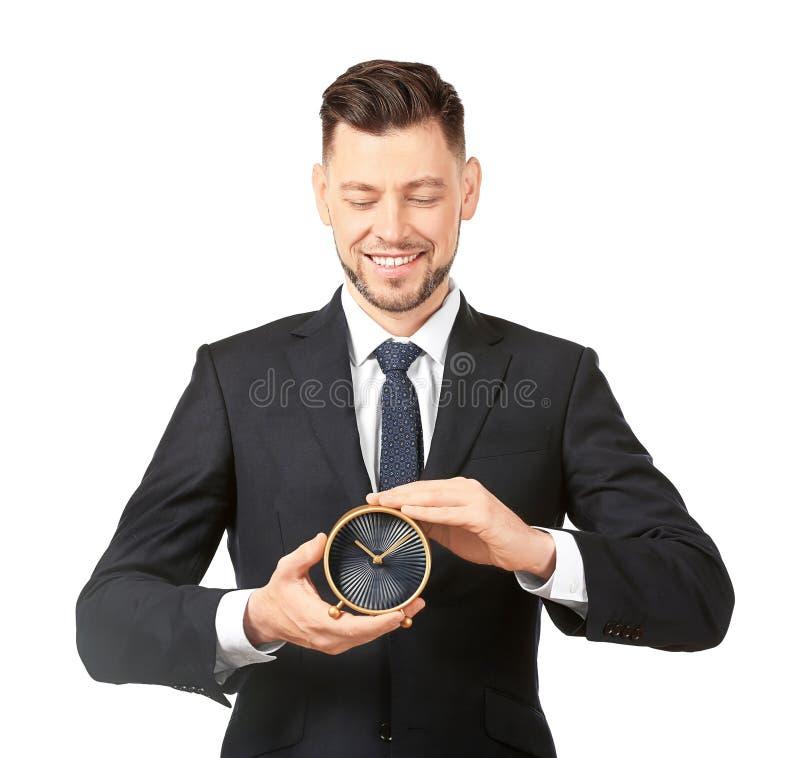 Despertador joven de la tenencia del hombre de negocios en el fondo blanco fotografía de archivo