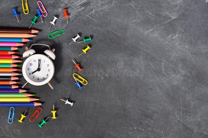 Despertador, lápices coloreados y efectos de escritorio en fondo negro del consejo escolar fotografía de archivo