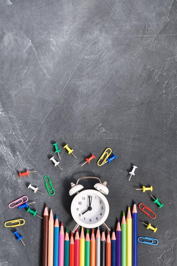 Despertador, lápices coloreados y efectos de escritorio en fondo negro del consejo escolar foto de archivo libre de regalías