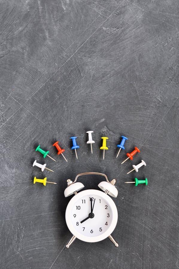 Despertador, lápices coloreados y efectos de escritorio en fondo negro del consejo escolar fotos de archivo