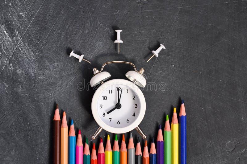 Despertador, lápices coloreados y efectos de escritorio en fondo negro del consejo escolar imagenes de archivo