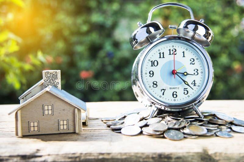 Despertador moderno en una pila de monedas y de casa colocadas fotografía de archivo libre de regalías