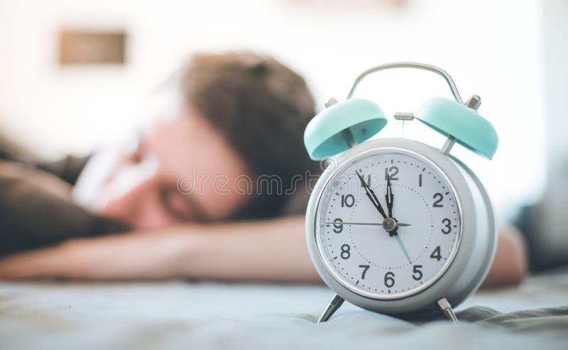 Despertador na manh? O homem novo dorme no fundo obscuro imagem de stock royalty free