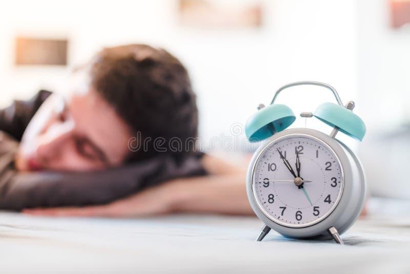 Despertador na manh? O homem novo dorme no fundo obscuro fotos de stock