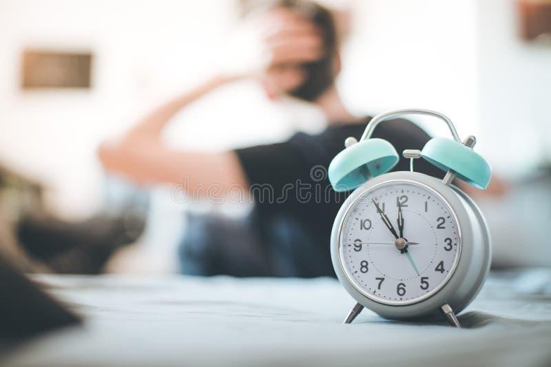 Despertador na manh? O jovem acorda e estica no fundo obscuro fotos de stock royalty free