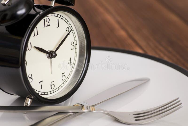 Despertador na placa com faca e forquilha no fundo de madeira Hora de comer Perda de peso ou conceito da dieta fotos de stock royalty free