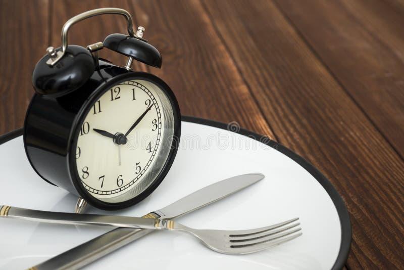 Despertador na placa com faca e forquilha no fundo de madeira Hora de comer Perda de peso ou conceito da dieta imagem de stock