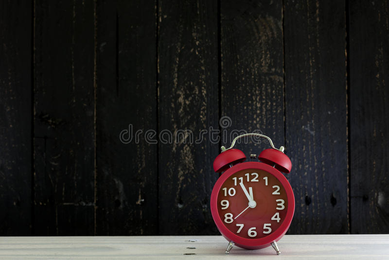 Despertador na tabela de madeira branca, cinco minutos a cloc do ` de doze o fotos de stock royalty free