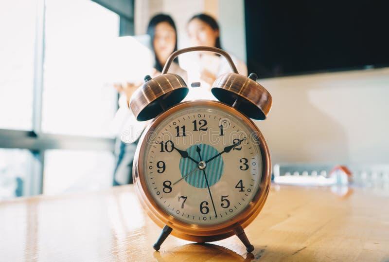 Despertador no fundo branco da tabela com os executivos na sala de reunião Gestão de tempo e pontualidade no conceito do trabalho fotos de stock royalty free