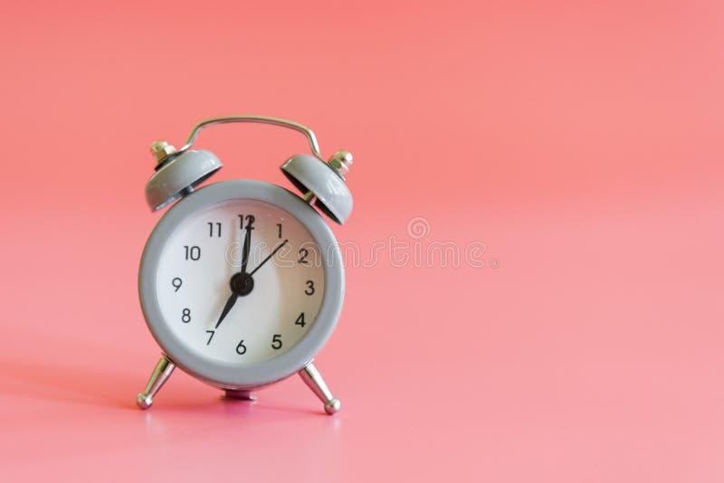 Despertador no fundo cor-de-rosa Despertador do estilo do vintage com espaço da cópia para o texto imagens de stock royalty free