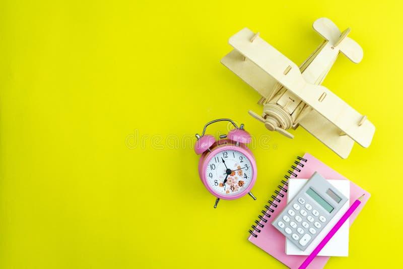 Despertador novo com avião de madeira, nota do Livro Branco do negócio, calculadora e lápis no fundo de papel amarelo fotos de stock