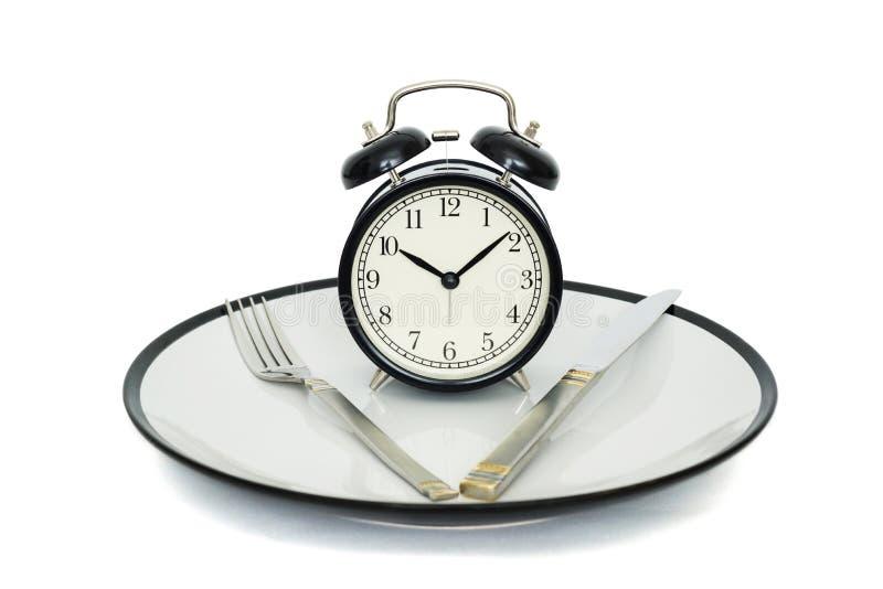 Despertador preto com forquilha e faca na placa Isolado no branco Hora de comer Perda de peso ou conceito da dieta imagem de stock