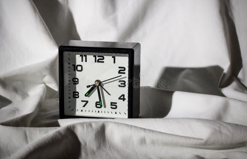 Despertador preto em uma folha branca com sombras duras fotos de stock