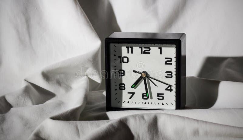 Despertador preto em uma folha branca com sombras duras foto de stock