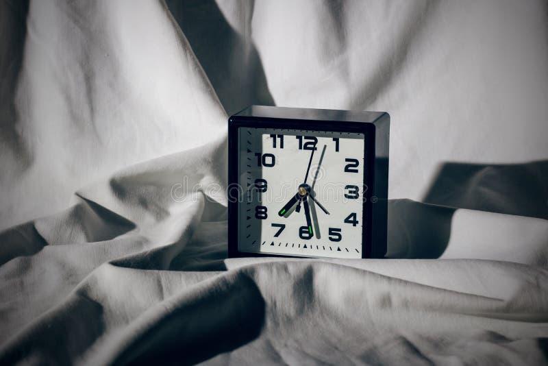 Despertador preto em uma folha branca com sombras duras imagens de stock