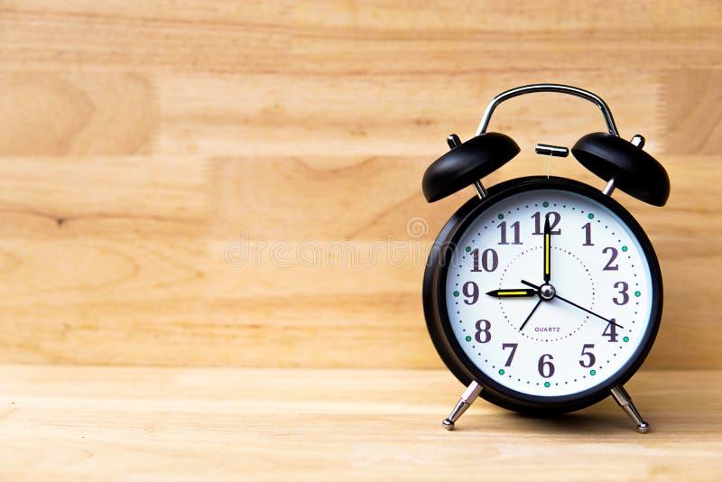 Despertador preto no assoalho e no fundo de madeira - conceito das épocas imagem de stock royalty free