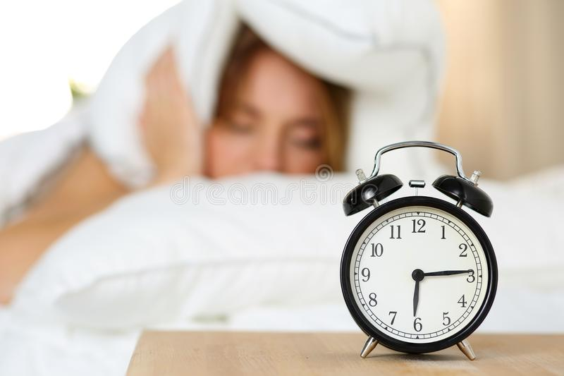 Despertador que se coloca en la mesita de noche que va a sonar fotografía de archivo libre de regalías