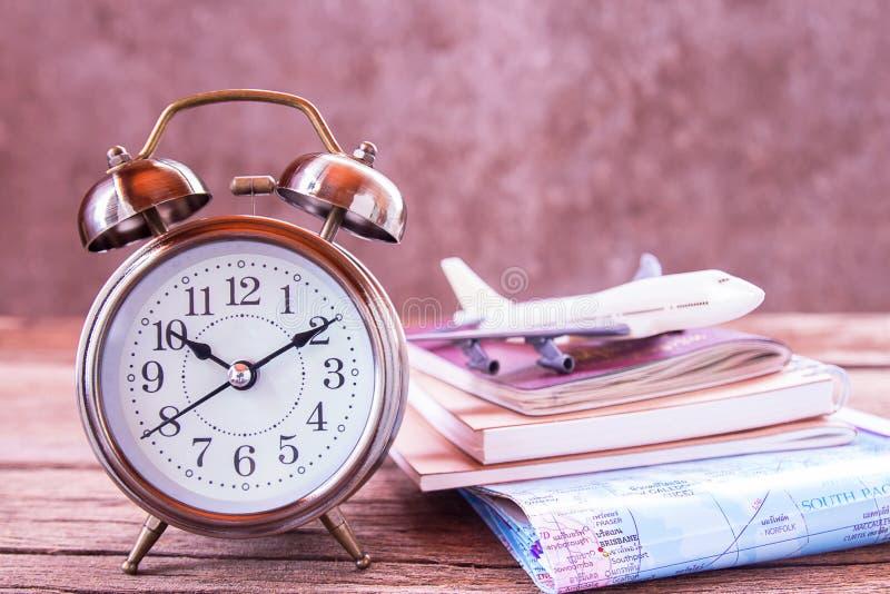Despertador retro, avião, mapa e caderno em uma tabela de madeira fotografia de stock royalty free