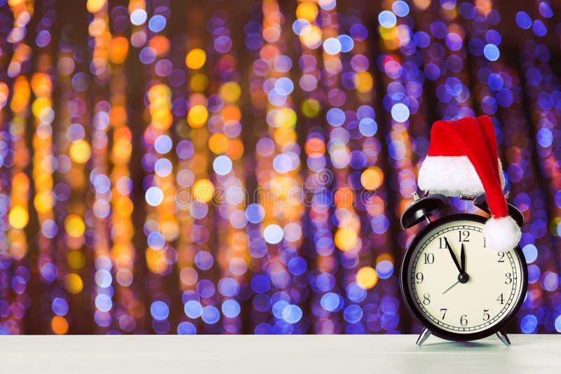 Despertador retro con el sombrero de Santa Claus contra fondo de hadas de las luces del bokeh de la Navidad que sorprende Copie e foto de archivo