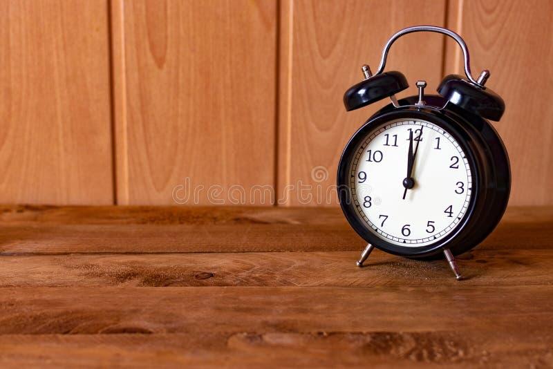 Despertador retro del color negro en una tabla de madera vieja imagenes de archivo