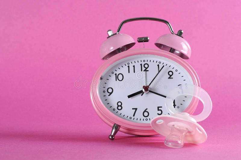 Despertador retro do estilo do vintage consideravelmente cor-de-rosa com pacificer do manequim do bebê fotografia de stock