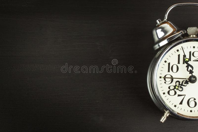 Despertador retro do metal em um fundo de madeira preto Abra seus olhos Alvorada a acordar Lugar para o texto fotos de stock royalty free