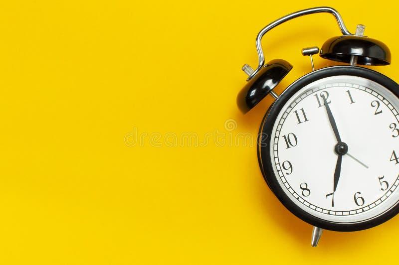 Despertador retro negro en espacio puesto plano amarillo de la copia de la opinión superior del fondo Fondo de Minimalistic, conc foto de archivo