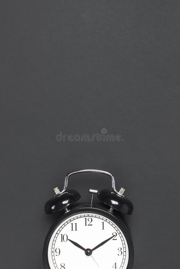 Despertador retro negro en espacio puesto plano oscuro gris de la copia de la opinión superior del fondo Fondo de Minimalistic, c imagenes de archivo