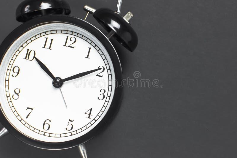 Despertador retro negro en espacio puesto plano oscuro gris de la copia de la opinión superior del fondo Fondo de Minimalistic, c imagen de archivo