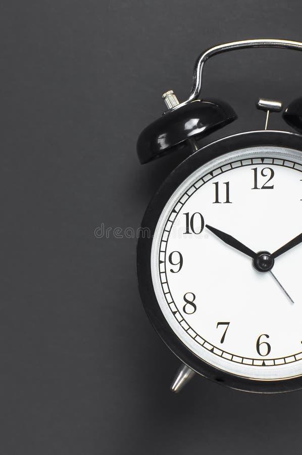 Despertador retro negro en espacio puesto plano oscuro gris de la copia de la opinión superior del fondo Fondo de Minimalistic, c fotografía de archivo